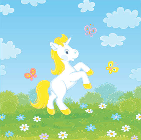Little white magical unicorn dancing with funny butterflies among colorful flowers on green grass of a field on a sunny summer day