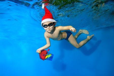 A little boy in a cap Santa Claus swims underwater with a gift in hand on blue background, looking at camera and smiling. Portrait. Shooting under water. Horizontal orientation