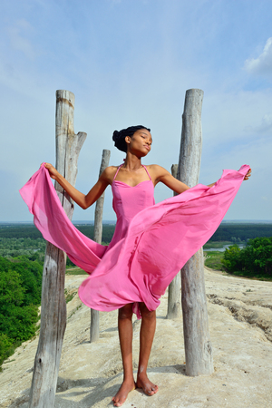 African American girl in a pink dress standing in the summer on a high hill near the tree against the sky and a beautiful landscape and plays with the dress in the wind.