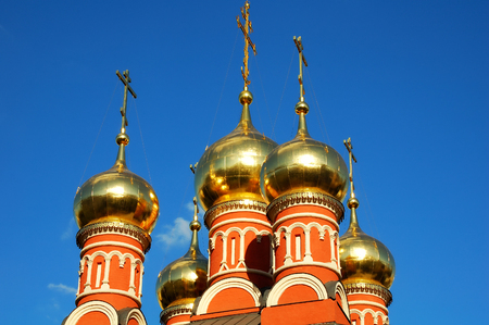 Golden domes with Orthodox crosses on the background of blue sky on the Church of St. Nicholas on the Chips, Moscow, Russia. Close-up. Horizontal view