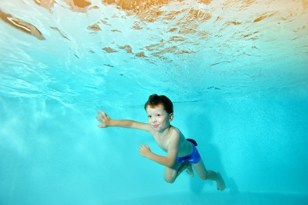 Happy boy swims underwater in the pool against the backdrop of bright lights, looking away and smiling. Portrait. Horizontal view.