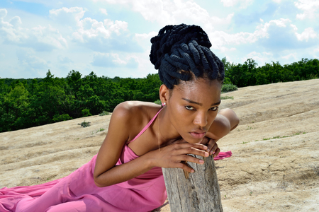 Sad African American girl lying in a pink dress on the mountain against the sky and clouds, leaning his hands on a dry tree and squinting looks at the camera. Portrait. Close up. Horizontal view.