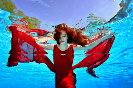 A charming girl with red hair swims underwater in the pool in a red dress on a blue background. She spread her arms out to the sides like a Seagull and looks down. Portrait. Standard-Bild