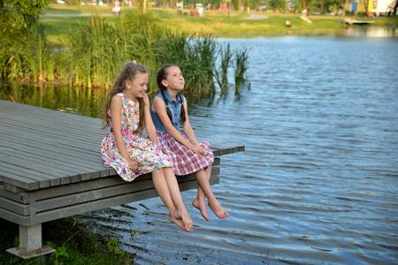 Glückliche Kinder, kleine Mädchen, sitzen und spielen bei Sonnenuntergang auf einer Holzbrücke am Fluss, plaudern mit den Füßen und lachen. Porträt. Landschaftsorientierung.