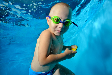 A little boy is swimming underwater in the pool on a blue background. He looks at the camera and smiles. Portrait. Horizontal orientation.