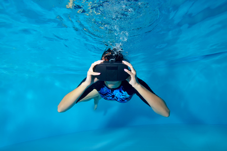 Virtual reality. A girl in a virtual reality helmet on her head swimming underwater in the pool on a blue background. Underwater photography. Horizontal orientation. Stock Photo
