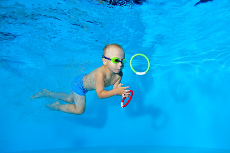 Sporty little boy swims to the toy underwater in the pool on a blue background. Portrait. Underwater photography. The horizontal orientation of the image.