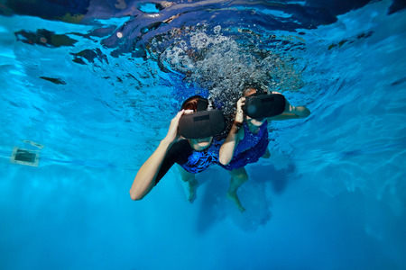 A woman and a child swim and play with virtual reality glasses on the head under the water in the pool. Shooting underwater. The horizontal orientation of the image.