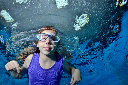 A little girl in swimming glasses is swimming underwater in the pool on a blue background and looking at me. Portrait. Close up. Bottom view. Underwater photography. Horizontal view of the image. Archivio Fotografico