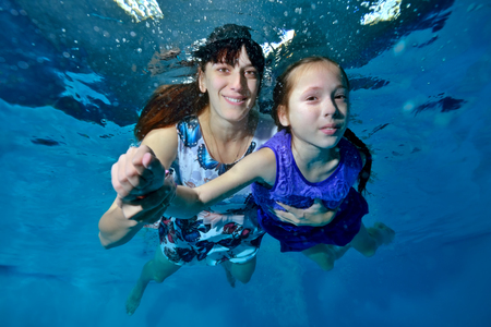 Mom and daughter swim underwater in the pool in beautiful dresses. Mom helps daughter. They look at the camera and smile. Portrait. Close up. Underwater photography.