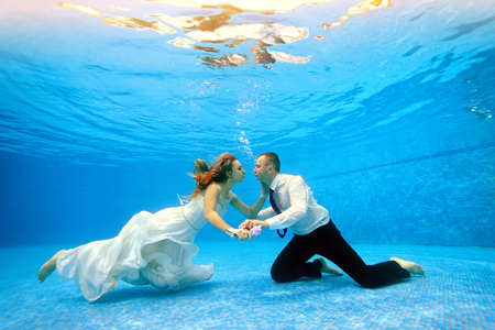 Loving couple in wedding dress swims underwater in the pool to meet each other. Horizontal view. Shooting from under the water Stock Photo
