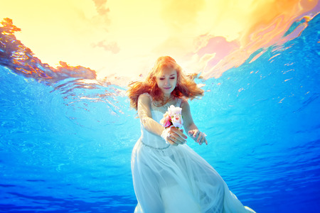 Incredible beauty redhead girl swims underwater in a wedding dress at sunset. Portrait. Horizontal view. Shooting from under the water