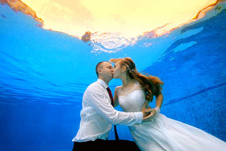 Happy man and woman in wedding dresses kissing underwater in the swimming pool on the background of a tropical sunset. Horizontal view. Shooting under water