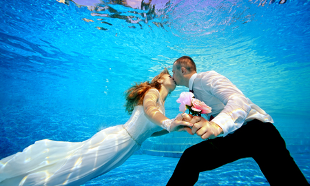 Lovers man and woman in wedding dresses kissing underwater in the pool and holding flowers in his hand. Horizontal orientation. A view from under the water from the bottom of the pool 스톡 콘텐츠