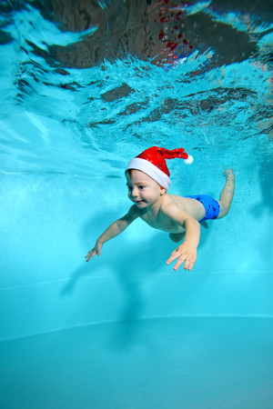 Beautiful baby in red cap of Santa Claus swims underwater in the pool on a blue background. Portrait. Shooting under water. Vertical orientation.