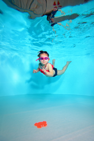Child underwater dives to the bottom of the pool after a toy on a blue background. Portrait. Shooting under water. Vertical orientation.
