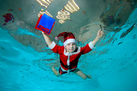 Little boy in costume of Santa Claus swimming underwater with a gift in hand on blue background, arms outstretched to the sides. Portrait. Shooting under water. Horizontal orientation.