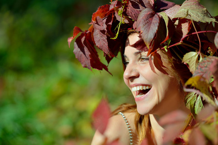 Joyful girl in a wreath of red and green leaves cheerfully laughs on the green background on a Sunny day. Фото со стока