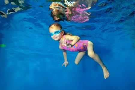 Niña feliz nada bajo el agua en la piscina mirando a la cámara y sonriendo. Retrato. Disparos bajo el agua. La orientación horizontal.
