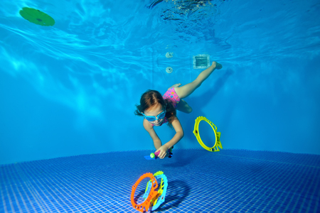 Little sports girl swims under water and picking up toys from the bottom of the pool. Portrait. Shooting under water. Horizontal view.