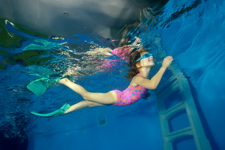 Sports little girl swims with fins underwater from the bottom of the pool to the surface and looks up. Portrait. Shooting under water. The landscape orientation. Foto de archivo