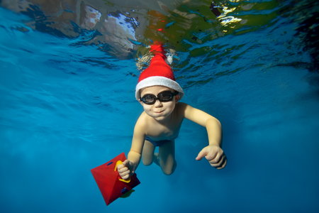 Happy child in a hat Santa Claus swims underwater with a gift in hand on blue background, looking at camera and smiling. The view from under the water. Horizontal orientation