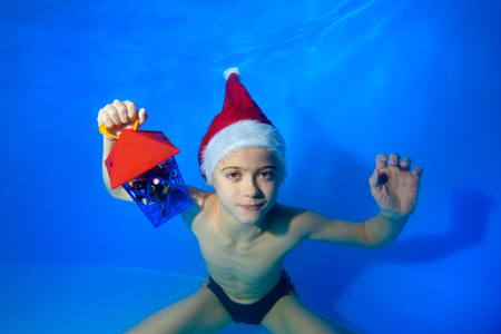 Portrait of a little boy who posing underwater at the bottom of the pool in a red hat of Santa Claus with a toy in his hand. He looks at the camera and smiles. Landscape orientation.