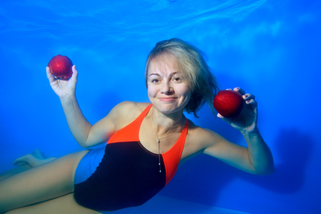 A charming girl posing underwater with red apples in her hands on a blue background, looks at the camera and smiles. Portrait. Landscape orientation.