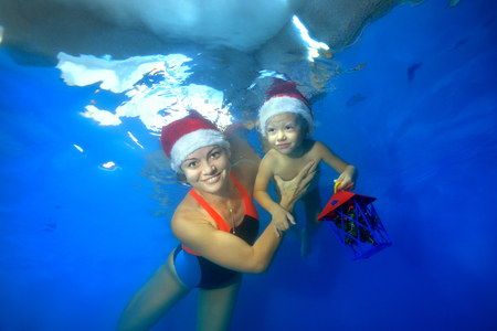 Mom supports the baby and helps him swim under water in the pool. They float in red Christmas caps on a blue background. The child holds a toy, and the mother looks at the camera and smiles.