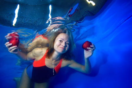 Beautiful girl floating under the water on a blue background and holding red apples in her hands. She looks at the camera and smiles. Portrait. Conceptual realism. 写真素材