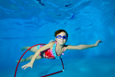 The child goes in for sports and swims underwater through a red Hoop at the bottom of the pool on a blue background and looks at me. Portrait. Landscape orientation. Underwater photography.