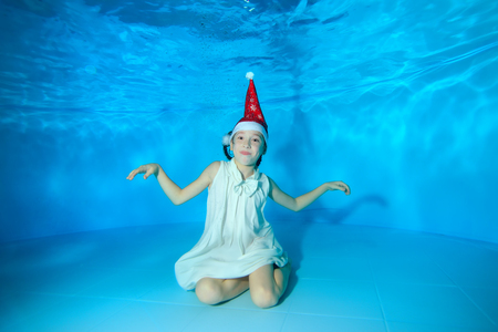 Cheerful little girl posing for the camera underwater at the bottom of the pool in a red Santa hat and white dress. She spread her hands apart, looks at the camera and smiles at the blue background.