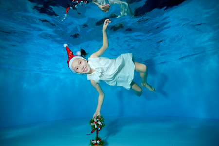 Smiling little girl playing underwater with a Christmas tree, which stands at the bottom of the pool. Baby swimming in Santa's red hat on blue background. Shooting underwater.
