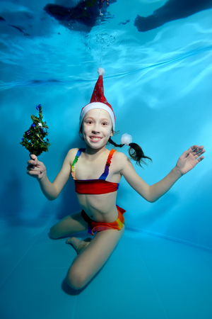Happy little girl posing under water at the bottom of the pool in a rainbow swimsuit and a hat of Santa Claus on a blue background, holding a small Christmas tree in his hand and smiling. Portrait. Foto de archivo