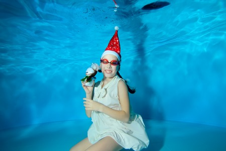 A little girl posing underwater in a red Santa hat and a white dress with a snowman in her hand. She sits at the bottom of the pool wearing swimming goggles, looks at the camera and smiles. Portrait.