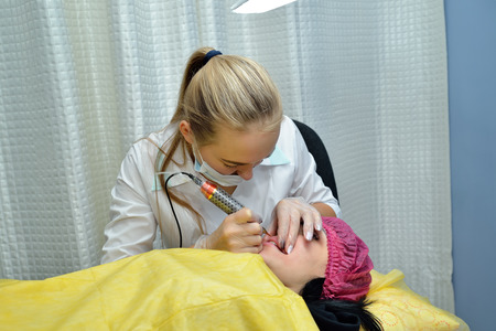 A master cosmetologist in a white medical gown makes permanent lip makeup for a young woman in a beauty salon and applies pink paint to her lips with a needle. Portrait. Landscape image orientation.