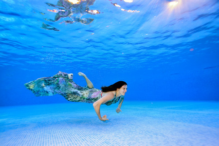Girl swims in a dress underwater near the bottom of the pool on a blue background and smiles. Portrait. Shooting underwater. Landscape view.