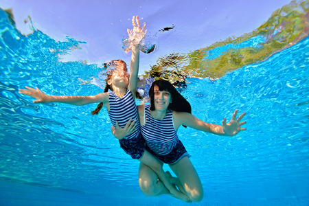 Happy mom and daughter swim and play underwater in striped bathing suits with their arms outstretched against the background of sunlight. Portrait. Shooting underwater. Horizontal view. Imagens