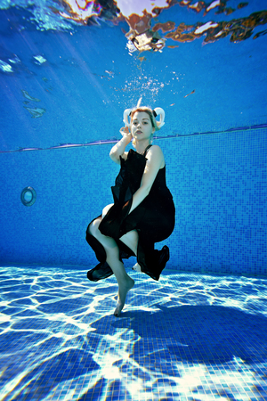Beautiful blonde girl posing underwater in the pool in a black dress and with white horns on her head on a Sunny day. Portrait. Cosplay. Shooting underwater. Vertical orientation of the image.