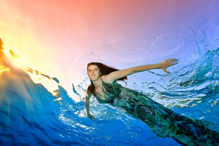 A beautiful model in a dress swims under the water in the pool against the background of sunlight on the surface, looks at the camera and smiles spreading his hands to the sides. Portrait.