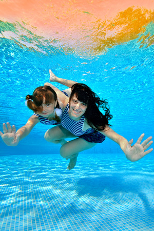 A little girl hugs her mother and swims with her under the water in the pool in striped bathing suits. They look at the camera and smile in the sunlight. Portrait. Underwater photography.