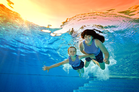 Happy family, mother and daughter, play sports on vacation and swim underwater in the pool in striped swimsuits on a bright Sunny day. They look at the camera and smile. Portrait. Bottom view. Imagens