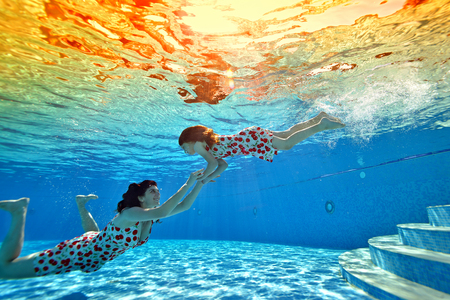 A little girl dives to her mother at the bottom of the pool on the background of a bright tropical sunset. Mom smiles and holds her daughters hands. Portrait. Shooting underwater from the bottom.