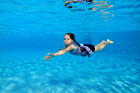 Little sports girl swims underwater in the pool in a striped swimsuit on a bright Sunny day, looking at the camera and smiling. Portrait. Underwater photography.