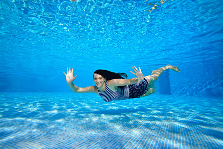 A cheerful sports girl swims under the water near the bottom of the pool in a striped swimsuit on a bright Sunny day, looks at the camera, waves her hands and smiles. Portrait. Underwater photography. Imagens