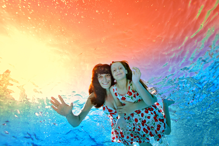 Mom and little daughter swim against the bright tropical sunset under the water in the pool, his arms outstretched. They hug, look at the camera and smile. Shooting underwater from the bottom.
