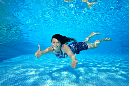 A beautiful girl goes in for sports and swims under the water near the bottom of the pool in a striped swimsuit on a bright Sunny day. She raised her thumbs up and looks at the camera. Portrait. Imagens