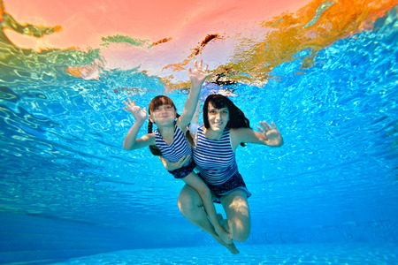 Mother and daughter swimming underwater in a striped bathing costumes on a background of sun rays. Portrait. Shooting underwater. Horizontal view.