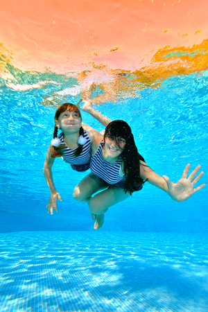Mom teaches her daughter to swim in the pool. They swim and play underwater in a striped bathing costumes on a background of sun rays. Portrait. Shooting underwater. Vertical orientation. Imagens