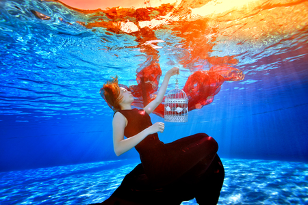 A fabulous girl in a beautiful dress in a pool swims and dreams on the background of bright lights. She holds a white cage in her hand and sinks to the bottom of the pool with her eyes closed.